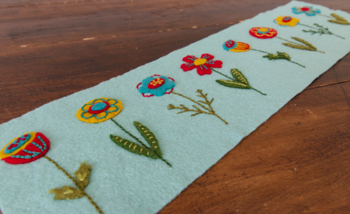 A long strip of embroidered felt flowers that will get stitched up to become the embroidered felt basket