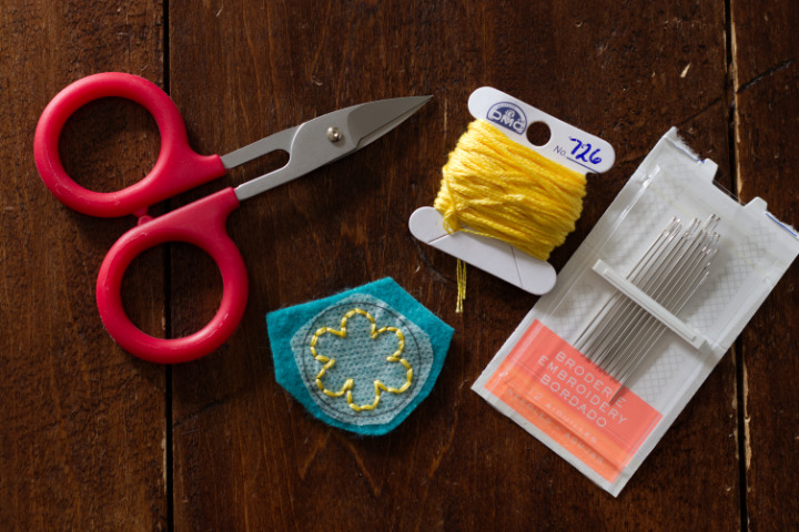 """Red """"Perfect Scissors"""" sit beside a stitched flower shape, yellow embroidery floss and embroidery needles"""