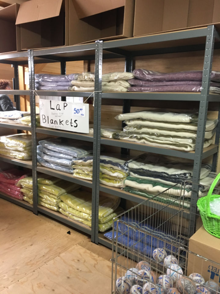 Shelves of Canadian wool blankets in lap size for sale in the mill in a variety of colours