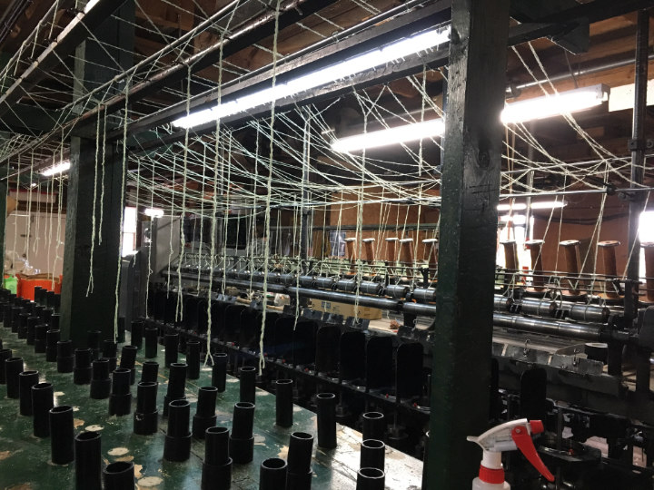 Large machines in the woollen mill with strands of yarn up overhead
