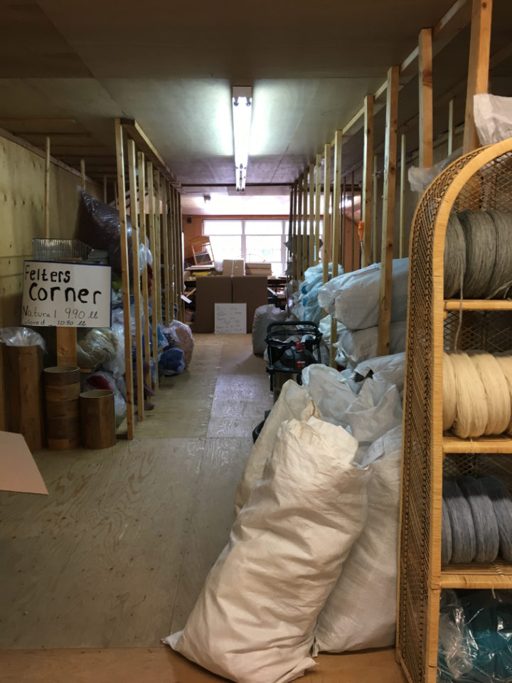 An aisle in the mill that has wool for felting for sale in large bags on shelves