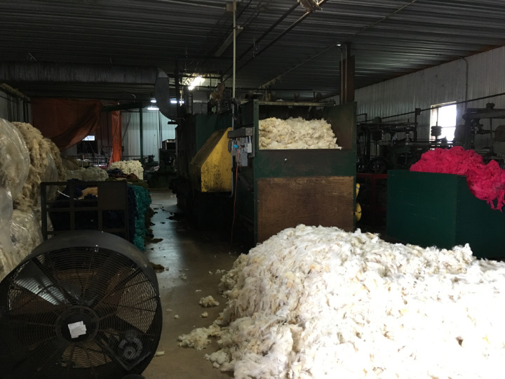 The washing and carding room of the woollen mill with large piles of raw wool and giant fans