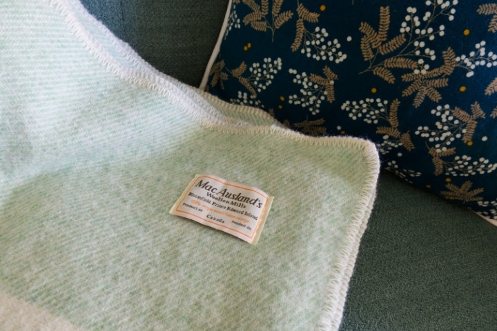 Label on green wool blanket - MacAusland's which makes Canadian wool blankets on PEI