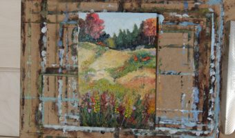 A small painting on a clipboard - a grassy, hilly meadow with trees turning fall colours at the horizon, and flowers in the foreground