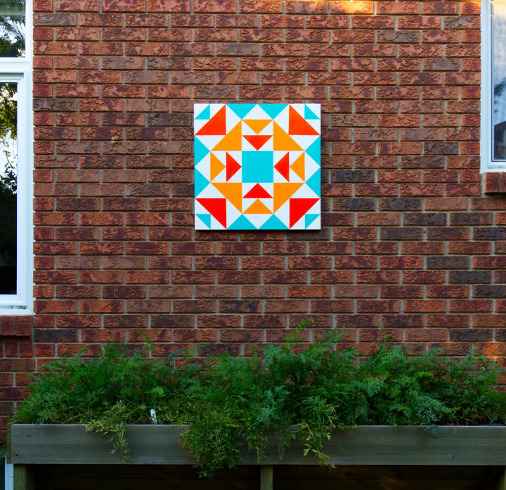 An orange and turquoise barn quilt hangs on a brick wall between windows and overtop of a raised planter of carrots
