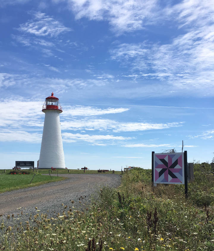 A purple and pink barn quilt on a sign by a lighthouse on PEI