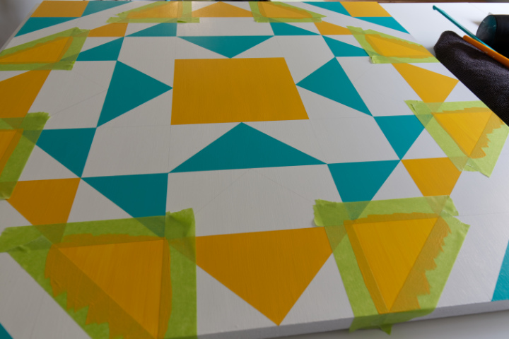 The yellow sections on the barn quilt have been taped and are being painted