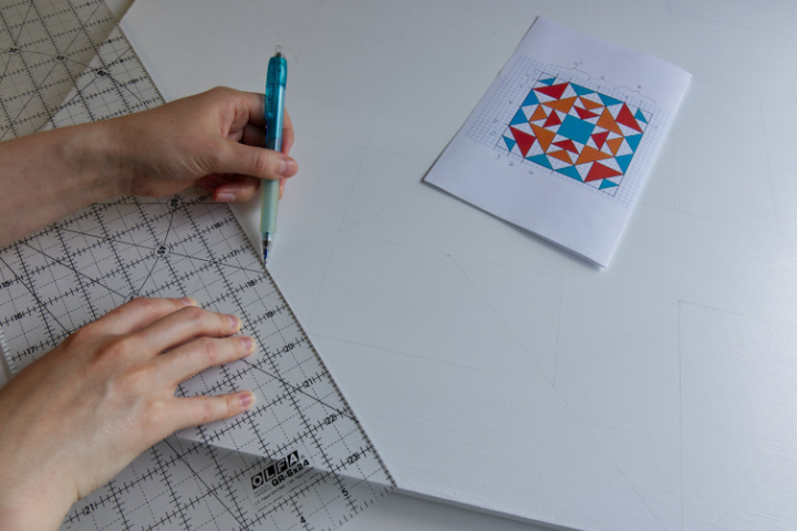Drawing out the design for the orange barn quilt with a quilting ruler and a pencil