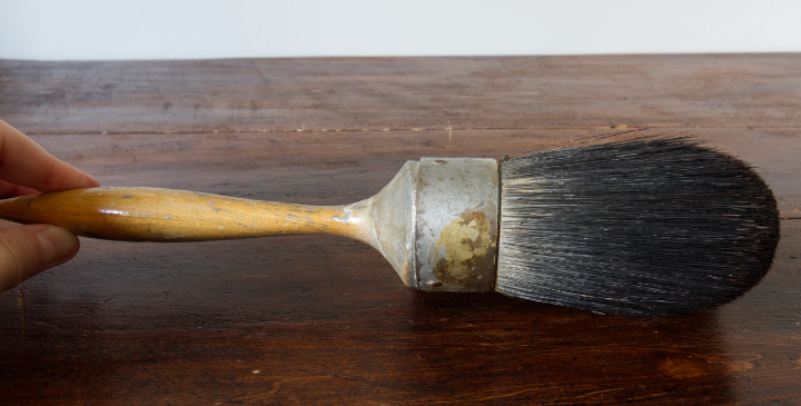 Fingers hold a vintage paintbrush, shown from the side profile and it's nearly round and very thick with bristles