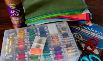 A stack of materials for felt embroidery including colourful wool-blend felt, an organizer of embroidery floss, Tacky Glue, scissors and printable stabilizer