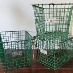 Three vintage wire metal locker baskets, rusting a little, with numbered plates on the front