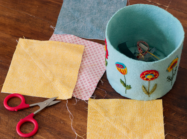 The Blooming Along basket sits beside half square triangles that have been sewn and are near open scissors as they are snipped apart