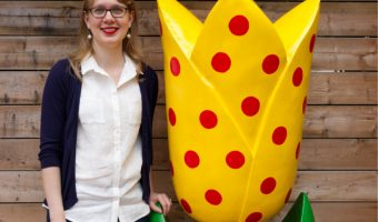 Danielle stands beside the finished tulip. They are nearly the same height. The tulip is yellow with red polka dots, green stem and leaves, and a turquoise base.
