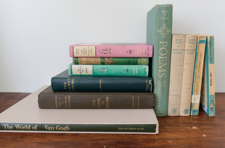 A group of vintage green, aqua, and one purple book, mostly vintage hardcovers