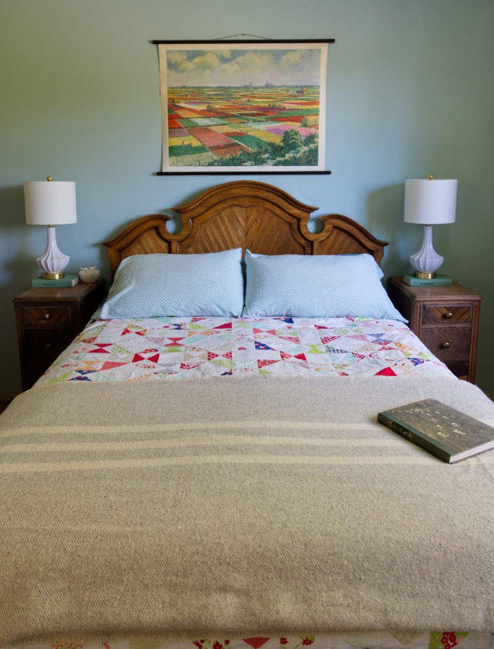 One of our Canadian wool blankets in a pale grey striped tweed lays folded across the end of a bed with a colourful quilt.