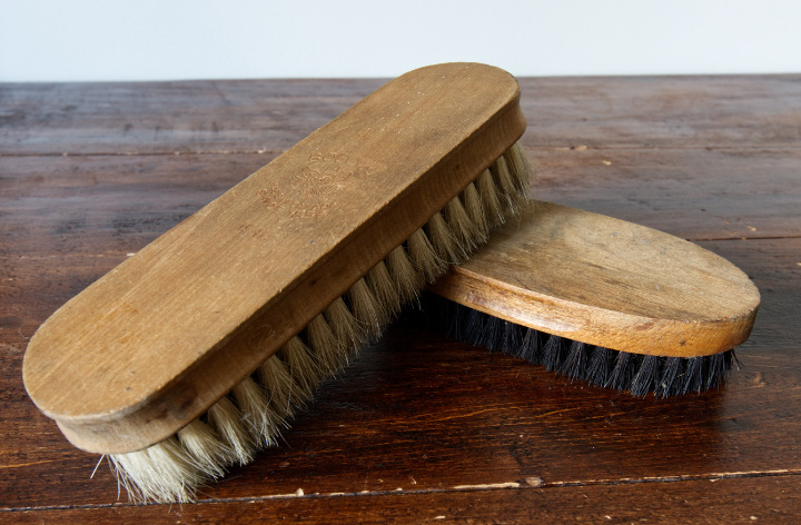 Two vintage brushes with wood handles for cleaning shoes or similar, one with white bristles, one with black