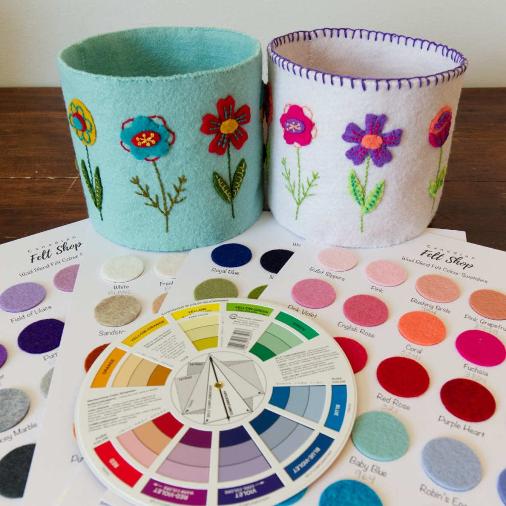 Choosing a felt colour scheme: Two felt Blooming Along Baskets in different colours sit beside felt swatches and a pocket colour wheel