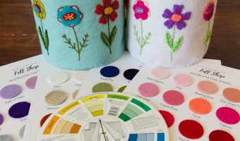Two felt Blooming Along Baskets in different colours sit beside felt swatches and a pocket colour wheel