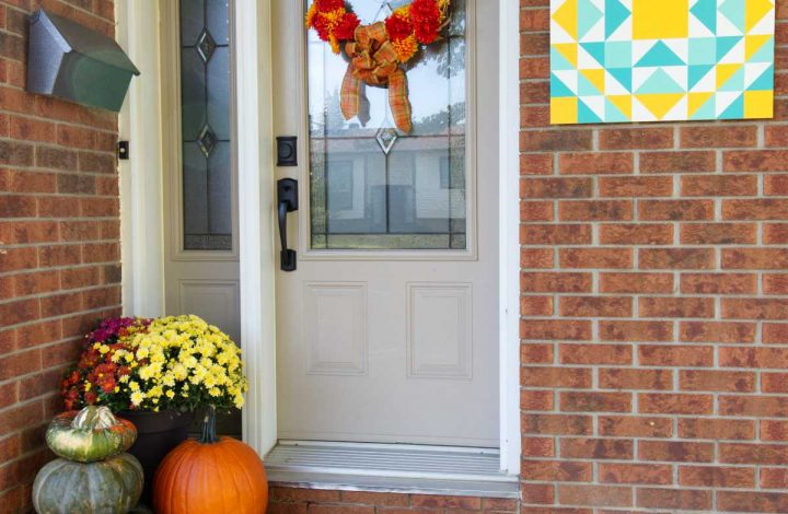 Fall front step with barn quilt hanging on brick wall in yellow and turquoise, fall wreath, mums, painted doormat and pumpkins