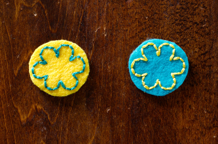 An example of high contrast stitching with two flower parts stitched, yellow and turquoise felt with the opposite stitching on each - choose a felt colour scheme with higher contrast