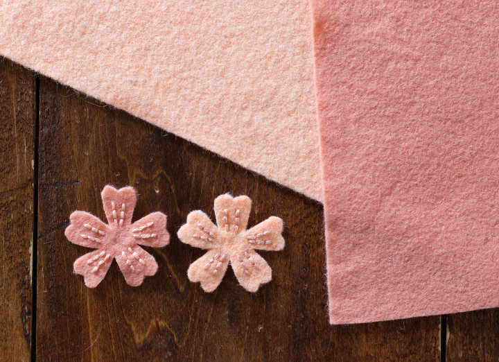 Two pink felts lay beside each other with two small pinks flowers with opposite coloured stitching, but low contrast because they're too similar